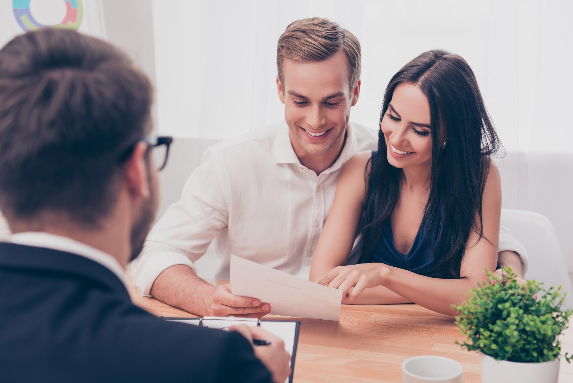 mladá dvojica sedí pri stole a pozerá na zmluvy