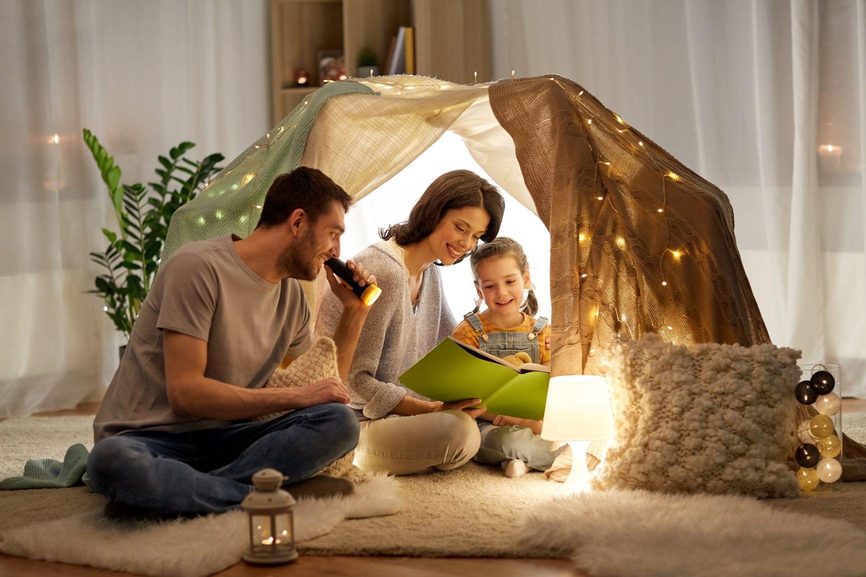 rodičia čítajú knihu dieťaťu v stane