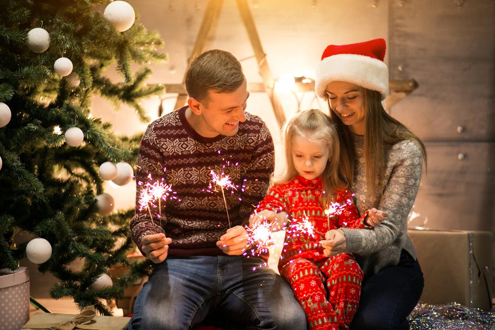 rodina pri vianočnom stromčeku páli prskavky
