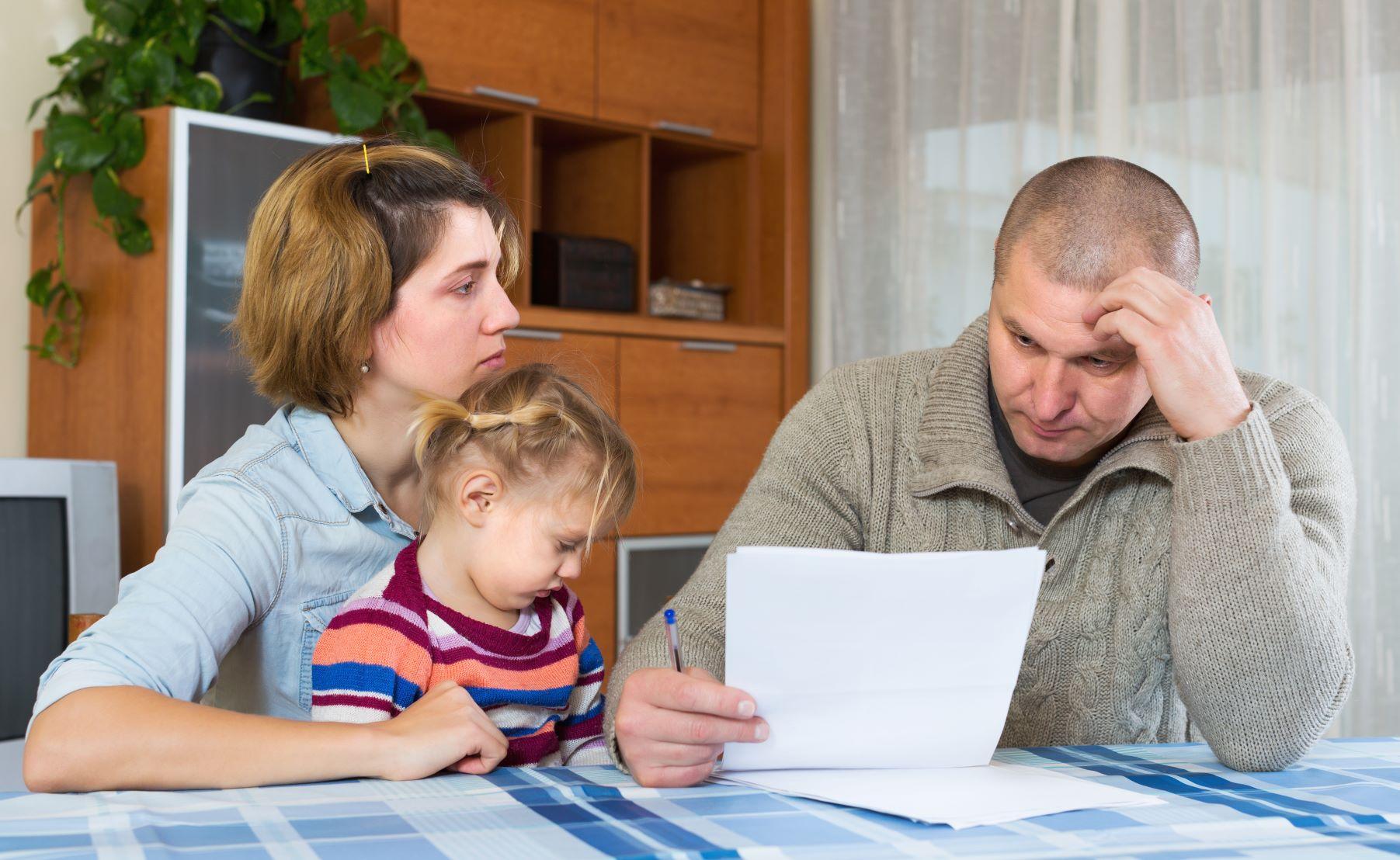 smutní rodičia a dieťa sedia pri stole