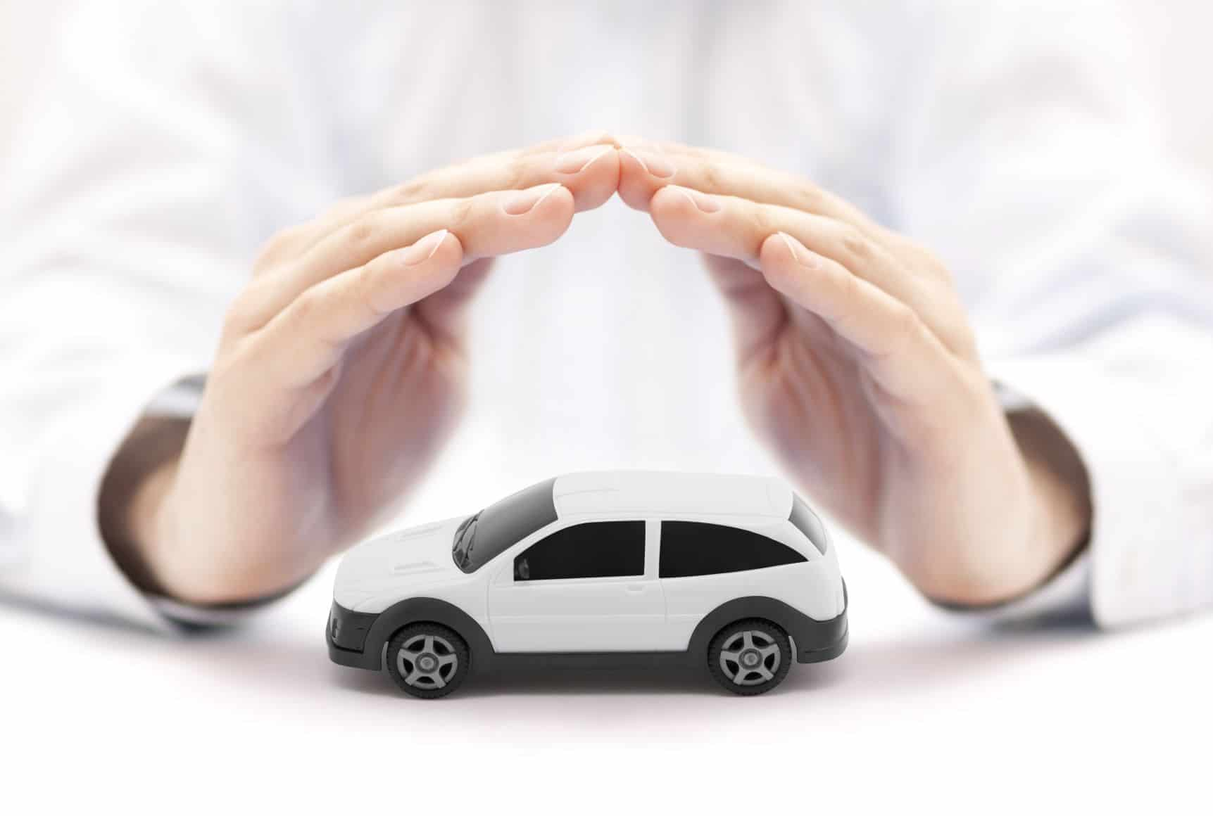 biele auto chránené rukami