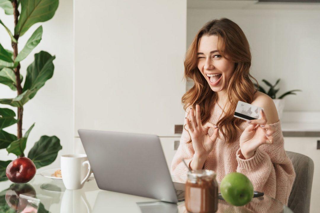 mladá žena s platobnou kartou sa smeje
