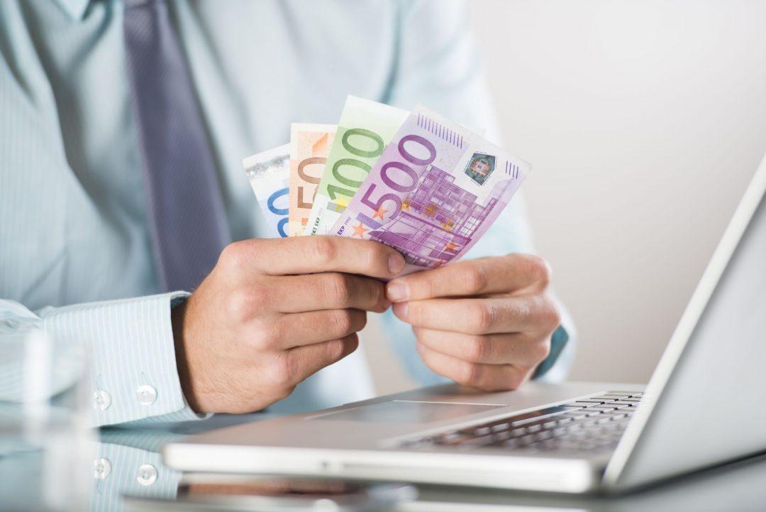 peniaze v ruke a počítač