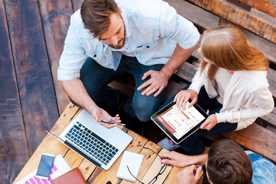 ľudia sedia pri stole pri počítači